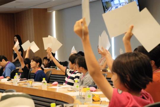 手を挙げて株券を示す子どもたち