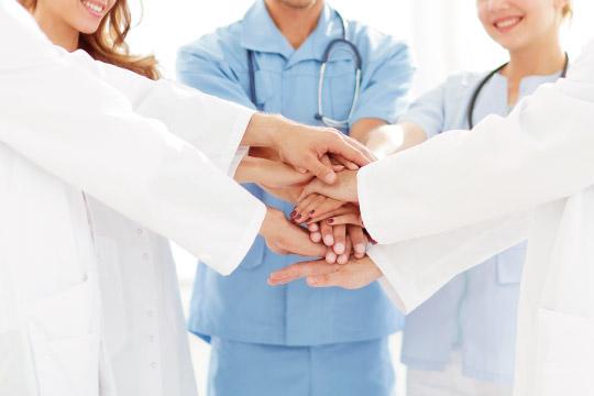 手を重ねる医師と看護師