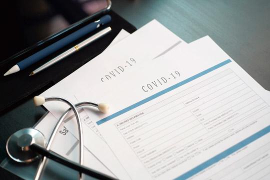 コロナウイルスと保険証券のイメージ