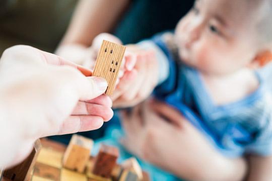 母親からおもちゃを受け取る赤ちゃん
