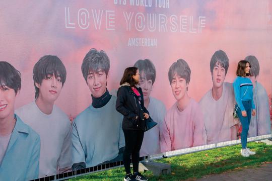 BTSのポスターの前で撮影するファン