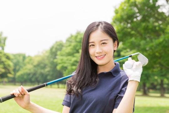 ゴルフをプレイする若い女性